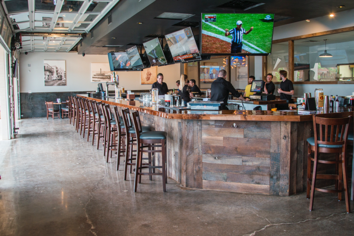 Dallas' 504 Bar & Grill has a rustic contemporary feel, with industrial features, garage doors and sliding barn doors that create an open-air space anchored by a four-sided bar.