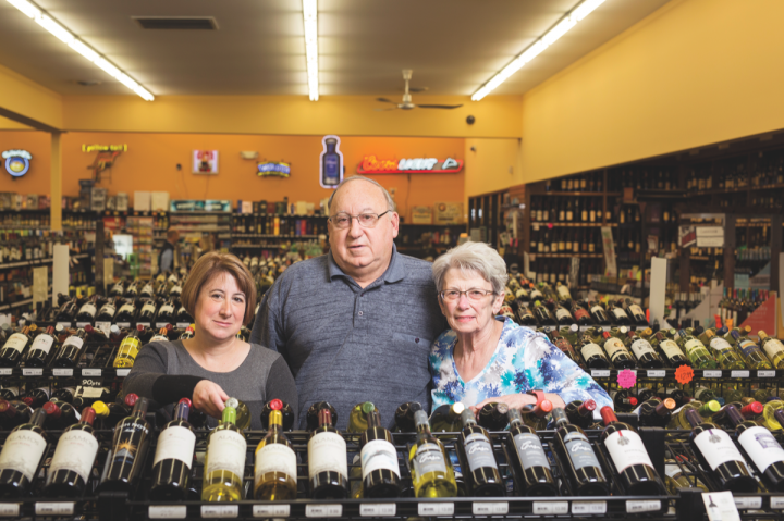 Charlie Key (center) founded Payless Liquors over four decades ago. He runs the company with his wife, Linda Key (right), and daughter, Liz Key (left).