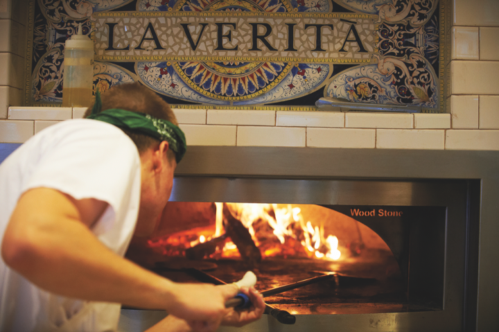 The osteria-style Pastaria is billed as Niche's approachable neighborhood venue. The menu features wood-fired pizzas (wood fire oven pictured) and traditional pastas alongside affordable Italian wines and a variety of brews.