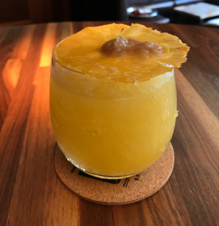 MKT's Island Fever blends aged dark rum, house-made passion fruit syrup, and fresh squeezed orange and lime juices. House-made pineapple wafer crisps are set ablaze with brown sugar and Everclear and added as a garnish.
