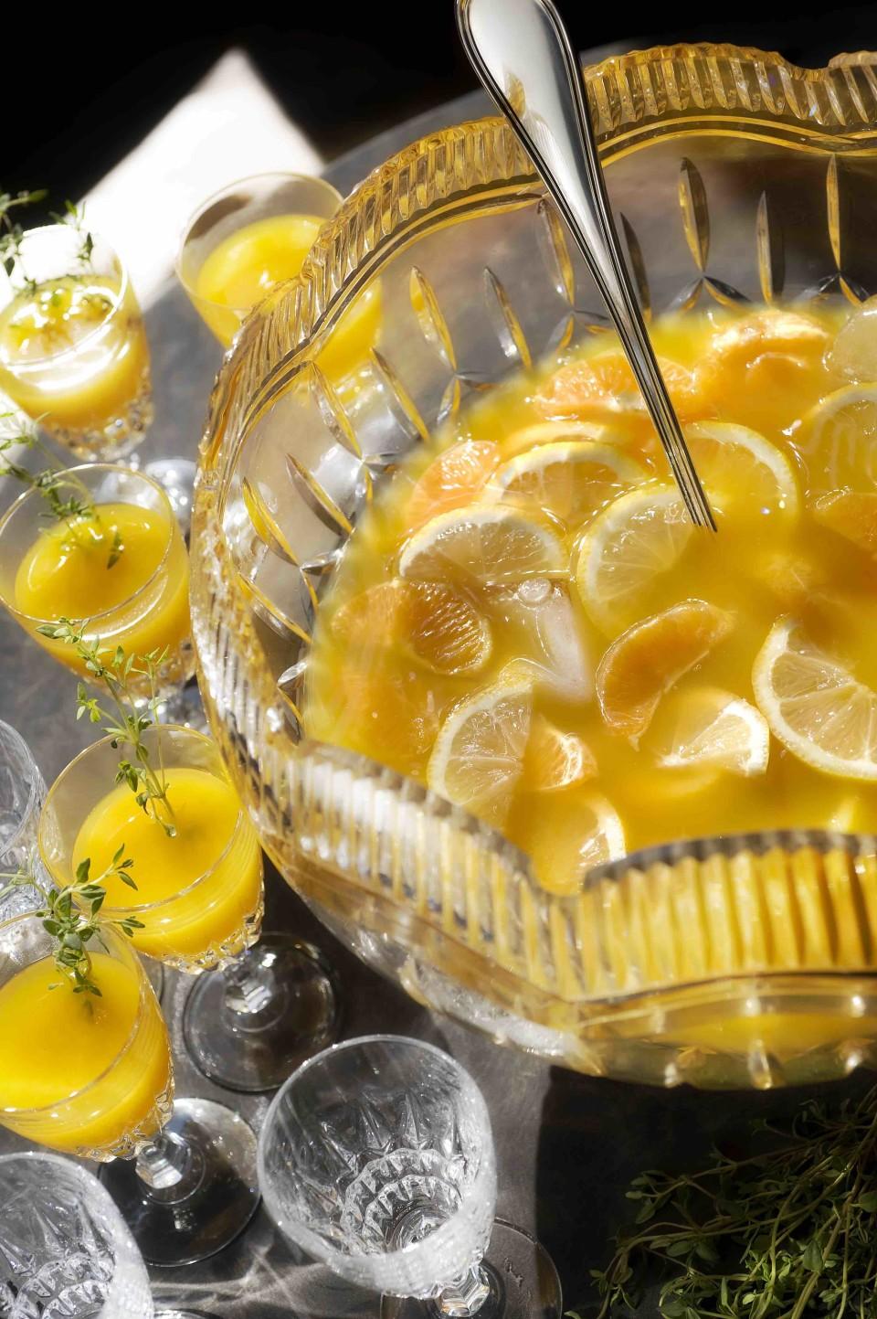 The Alchemist Punch features Bénédictine liqueur, orange purée, lemon, honey, orange and tangerine wedges, cinnamon, cloves, and thyme.