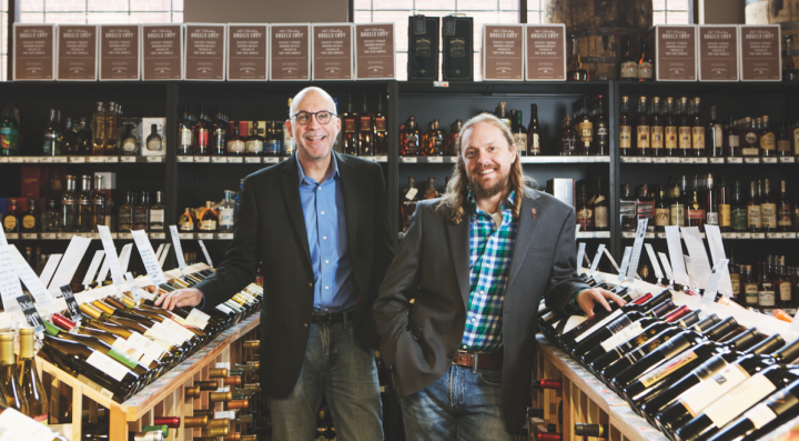 Jason Main (right) co-owns The Wine Merchant and serves as vice president, while Tom Nicholson (left) is the general manager and sole wine and spirits buyer. The store was founded by Charles Prince in Clayton, Missouri, in 1992.