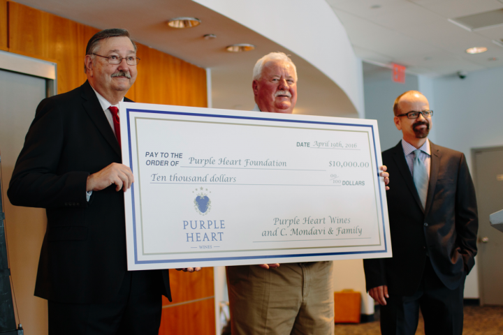 Purple Heart Foundation chairman Jeff Roy (left) accepts a check from C. Mondavi & Family winemaker Ray Coursen (middle) and vice president of marketing Paul Englert (right).
