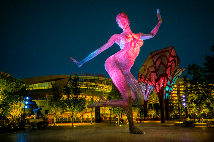 The Park features a desert landscape with indoor and outdoor seating areas and decorative elements, including a 40-foot-tall sculpture of a dancing woman.