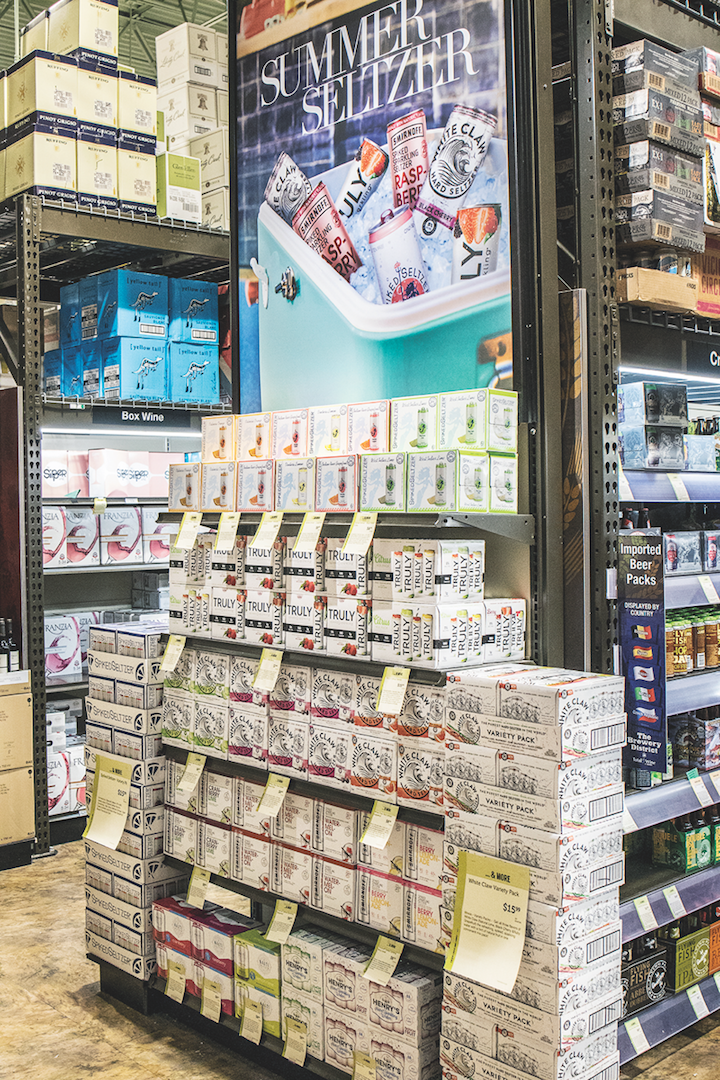 Cans are the preferred container for hard seltzers, as they are lighter and more portable than bottles, enabling consumers to enjoy them in varying locations (Total Wine & More hard seltzer display pictured).