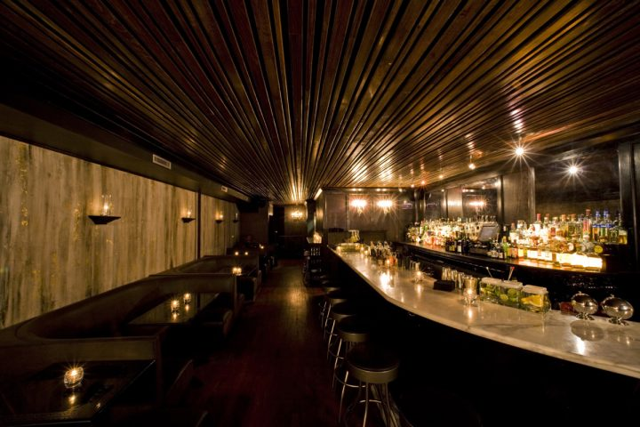 Death & Co. (interior pictured) features a dim and moody ambiance, with candlelit tables, a white marble bar, and leather seating.