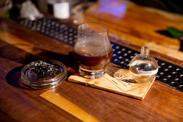At District in Los Angeles, the Nicotine (pictured) blends cacao nib-infused Nonino Quintessentia amaro with white rum, mezcal, dry curaçao, slivovitz, and espresso, and is served in a smoked glass.