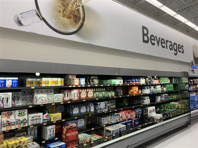 Walmart (East Fishkill, New York beer shelves pictured) is streamlining its e-commerce options for beverage alcohol in 29 states, allowing customers to order on the store website or the Walmart Grocery app.