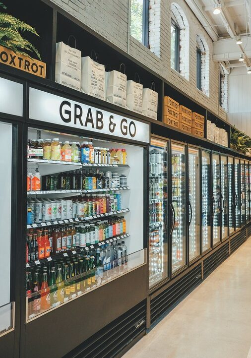 Foxtrot (grab and go coolers pictured) offers food and drink bundles, including hard seltzer with chips and guacamole.