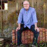金宝博手机酿酒师兼Ramey创始人David Ramey坐在一堆砖块上,前面是一座风化的木质外屋