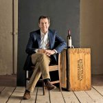 潘福尔斯首席酿酒师彼得·加戈的肖像与酒瓶和木箱坐在一起金宝博手机