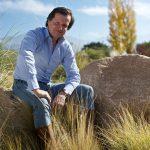 Portrait of vintner François Lurton outside sitting on large rocks amid tall grass