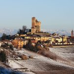 Scenic landscape of the village of Serralunga d'Alba flanked by snow-covered Nebbiolo vineyards