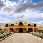 Bodega Piedra Negra winery flanked by rows of rose bushes and grapevines