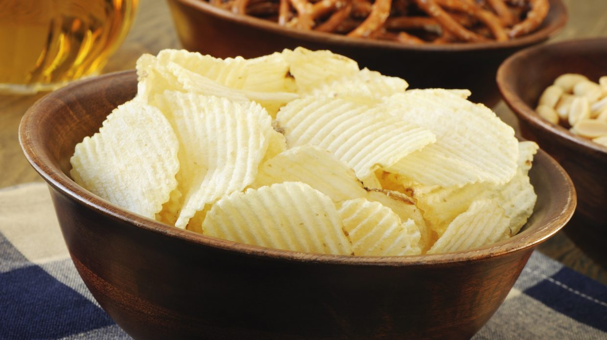 A large bowl full of ruffled potato chips sits in front of a bowl of pretzels, a bowl of peanuts, and a glass of dark alcohol.