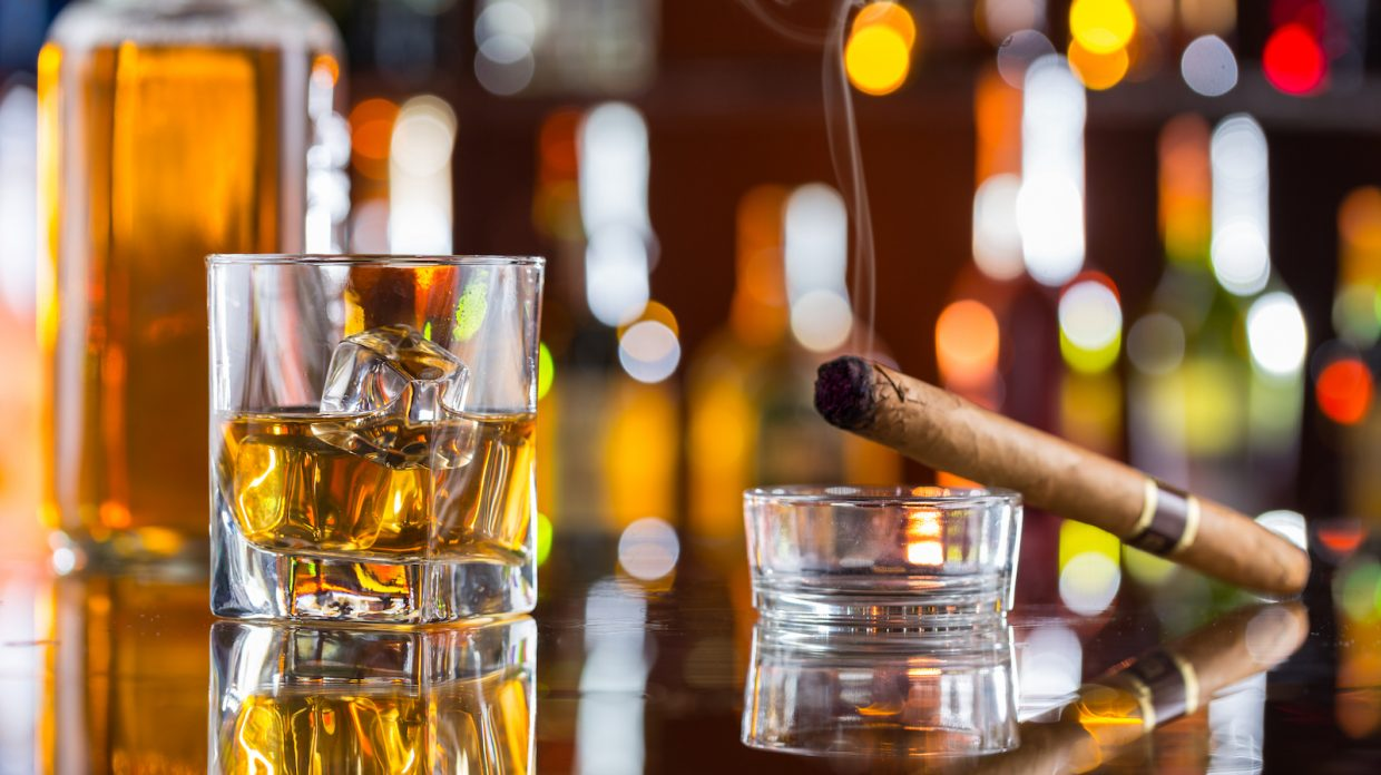 Whiskey drink with smoking cigar on bar
