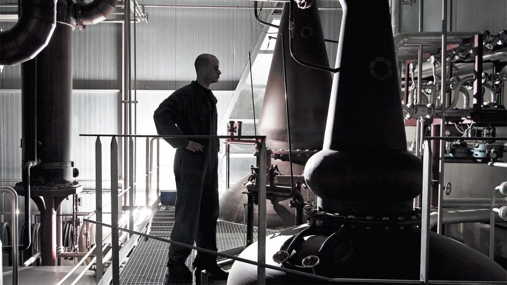 a distiller observes the pot stills at Warenghem Distillery in Brittany, France, where Armorik single malt whisky is made