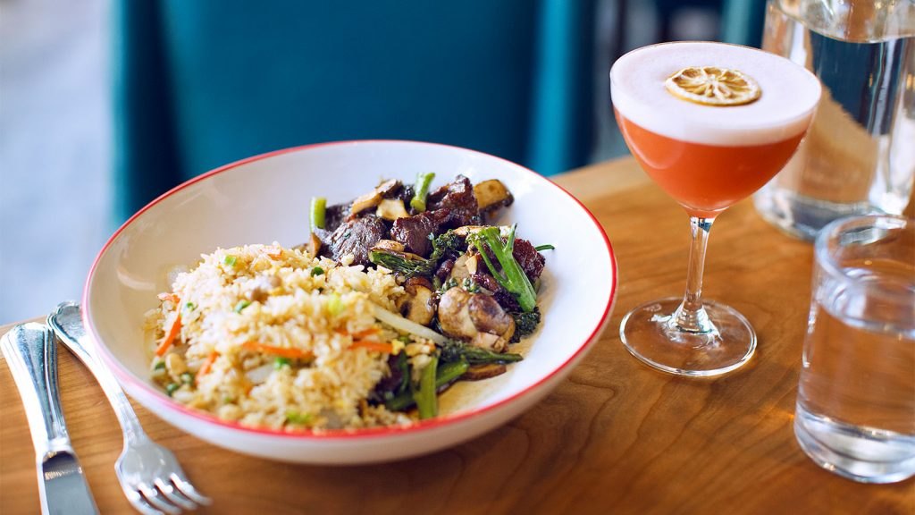 A colorful dish and a vibrant cocktail at Farmers & Distillers in Washington, D.C.