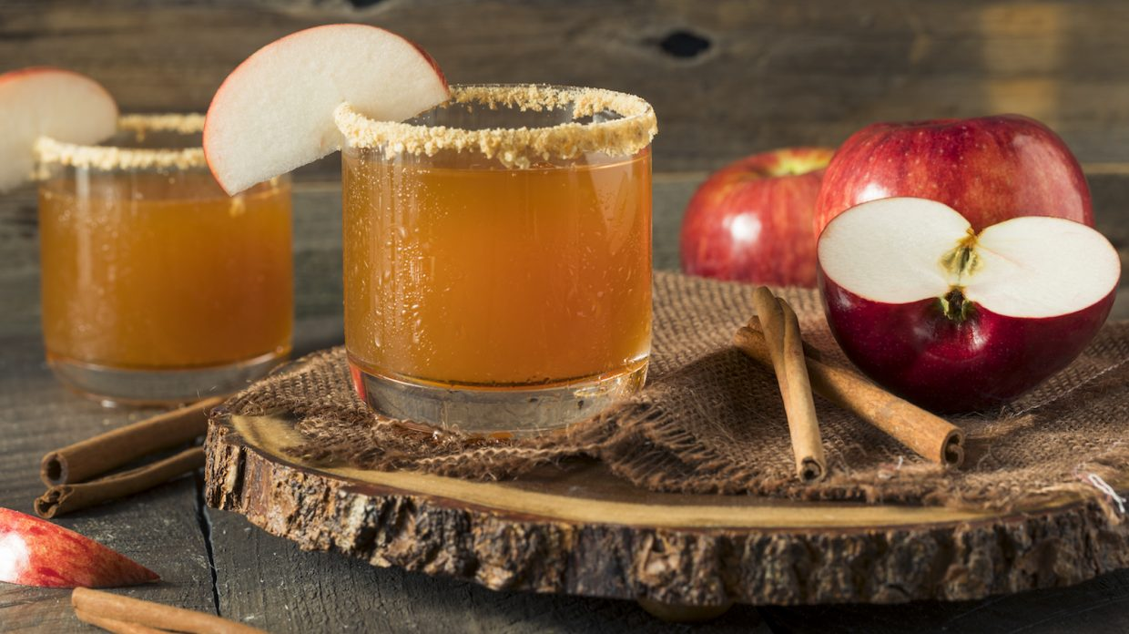 brown cocktail in rocks glass with a slice of apple on the rim and cinnamon sticks and apples in the background