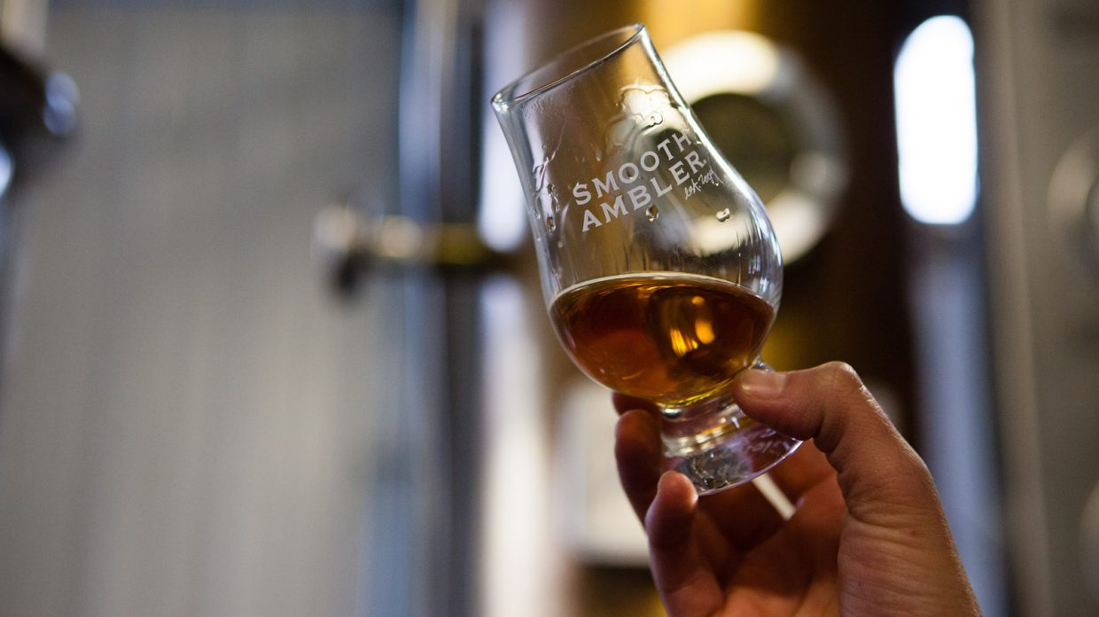 """A hand holding a Glencairn glass of whiskey that says """"smooth ambler'"""