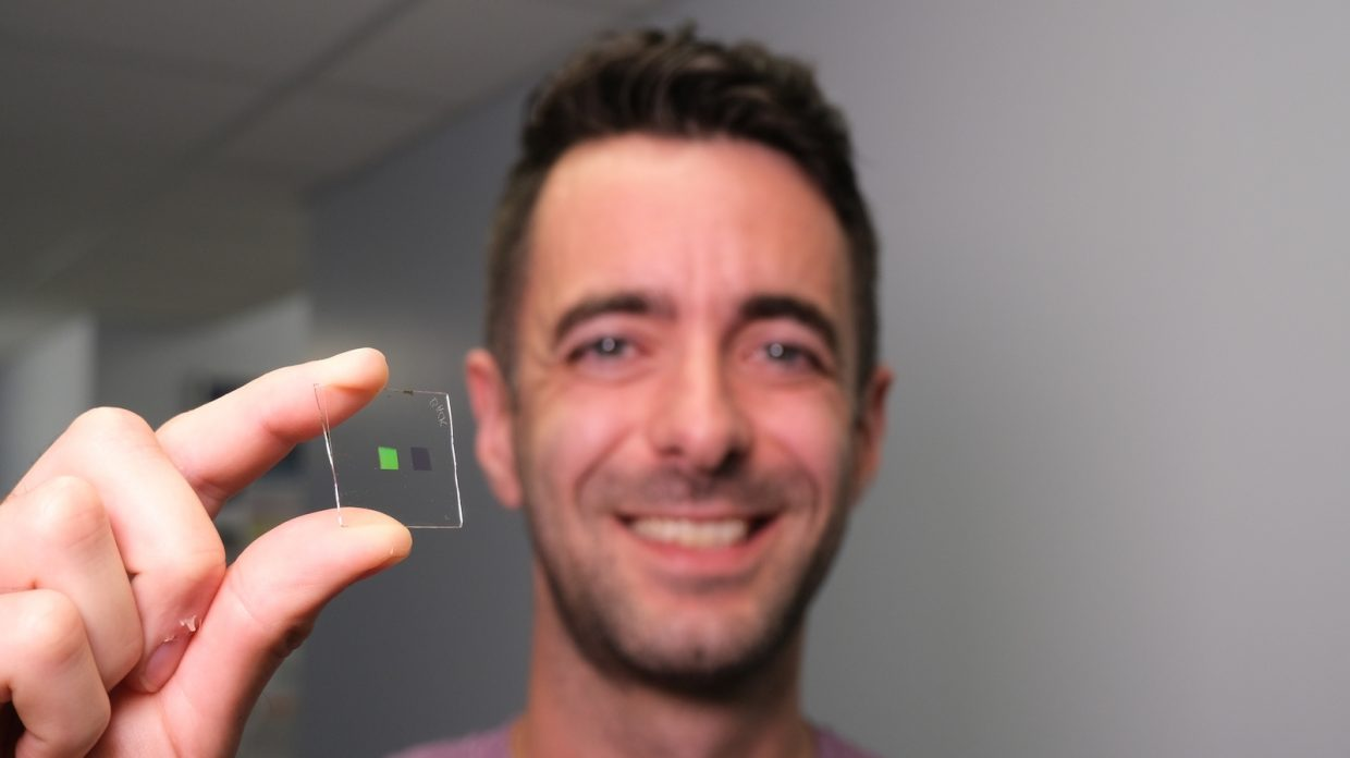 Scottish researcher Alisdair Clark holding a transparent square about 1 inch by one inch