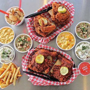 Generously-sized pieces of hot chicken topped with pickle slices rest in baskets surrounded by sundry side dishes including what appear to be beans of some sort, possibly black-eyed peas, macaroni and cheese, potato salad, and french fries at Hattie B's Hot Chicken in Nashville, Tennessee.