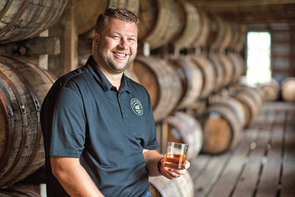 Jim Beam master distiller Freddie Noe sits on top of a whiskey barrel that is resting on its side, holding a glass of whiskey in his left hand and smiling.