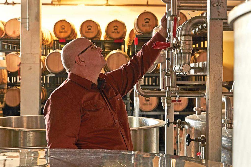 Distiller Herman Mihalich stands in Dad's Hat Distillery amid distilling equipment.