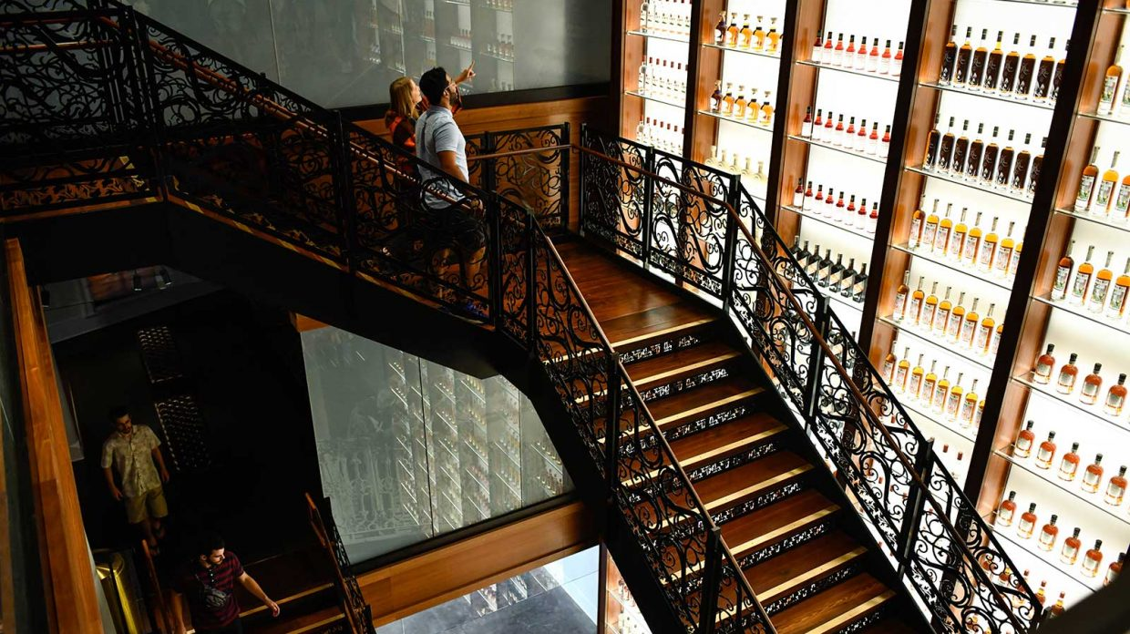 Visitors at the newly opened Sazerac House cocktail museum in New Orleans descend a staircase past a three-story bottle wall showcasing various Sazerac spirits.