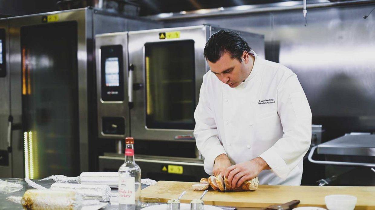 Sébastien Giannini, executive chef at Kingbird restaurant at the Watergate Hotel in Washington, D.C., slices a turkey roulade atop a cutting board in a restaurant kitchen.