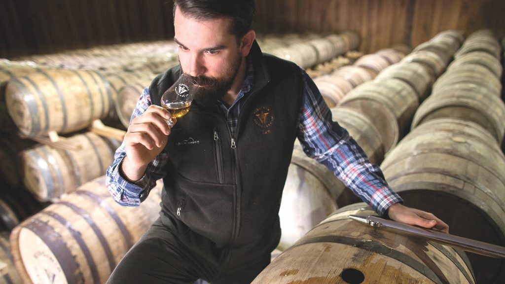 Ian Thomas crouches down between some barrels so sniff a glass of whiskey.