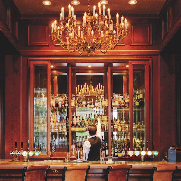 A well-dressed male bartender reaches for a bottle in the elegant bar of the Intercontinental Hotel in Dublin. A large candelabra hangs above the bar.