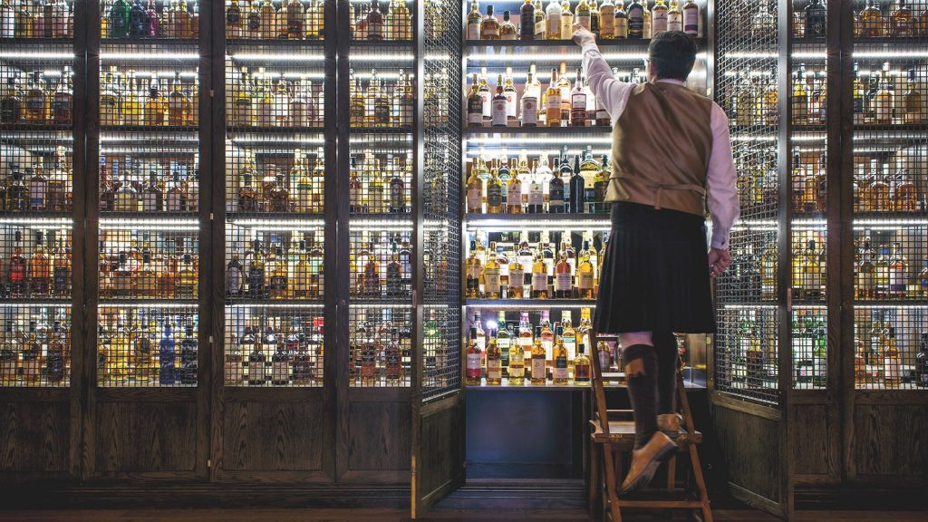 A man in a kilt reaches for a bottle of whisky in a very packed cellar in the bar Scotch at the Balmoral Hotel.