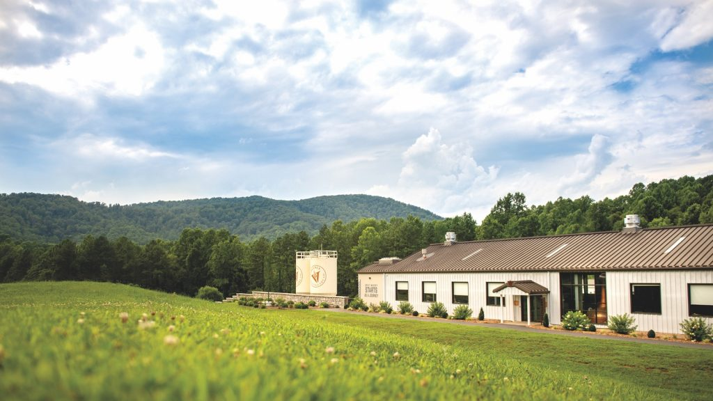 The Virginia Distillery Company sits on a large patch of green fields on a lightly cloudy day.