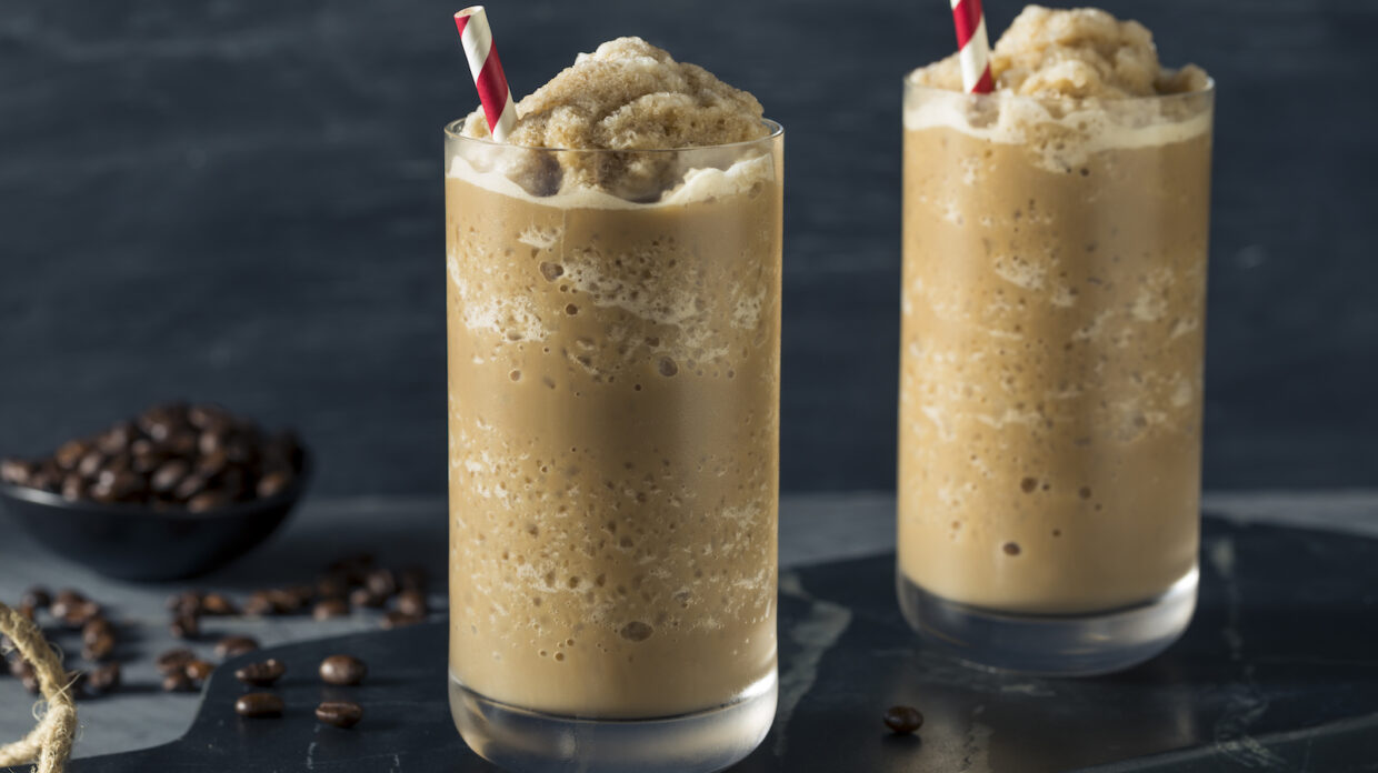 Two frozen coffee drinks sit in front of some coffee beans.