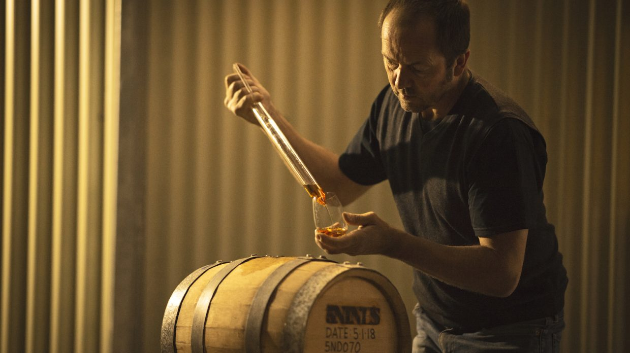 A man pipes whisky from a barrel to a glass.