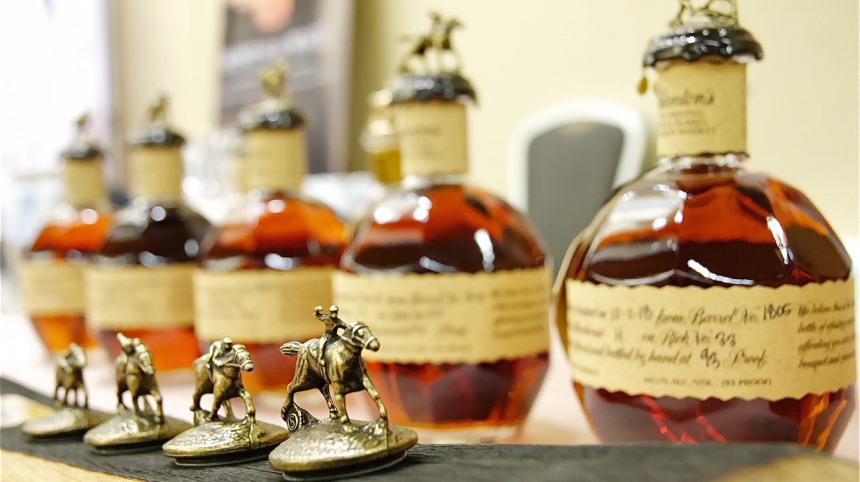 Four whisky stoppers topped with jockey and horse figurines sit in front of out-of-focus Blanton's whisky bottles.