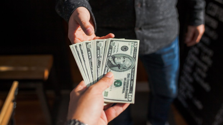 A man hands another man a large stack of ten-dollar bills.