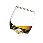 The Sagaform Rocking whisky glass is shown rocking back and forth and containing about an ounce of whisky.