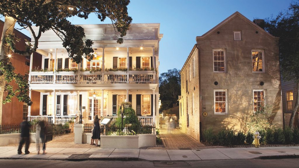 A large white two-story antebellum building sits next to an equally large brown building during sunset.