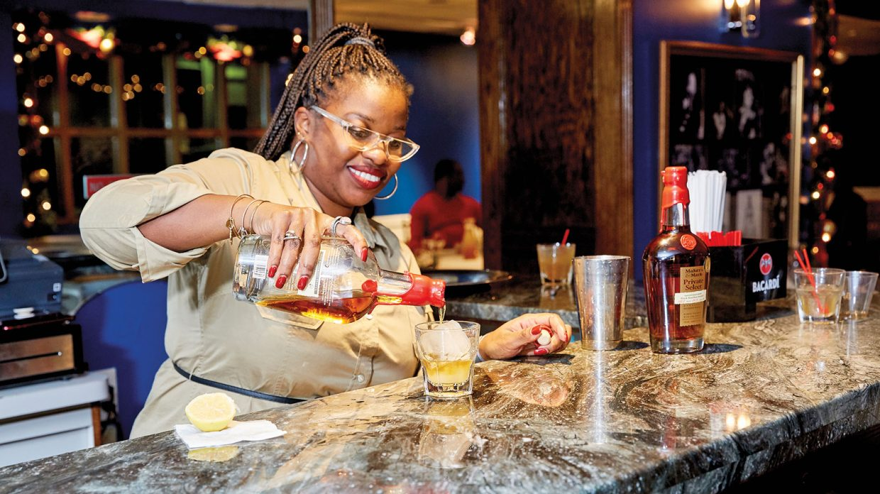 A woman wearing red lipstick and nail polish, hoop earrings and bracelets, her braided hair in a ponytail, pours from what appears to be a bottle of Maker's Mark Private Select bourbon over a large ice cube in a rocks glass resting atop what appears to be a marble bar at Sylvia's Restaurant in Harlem on Dec. 5, 2019.