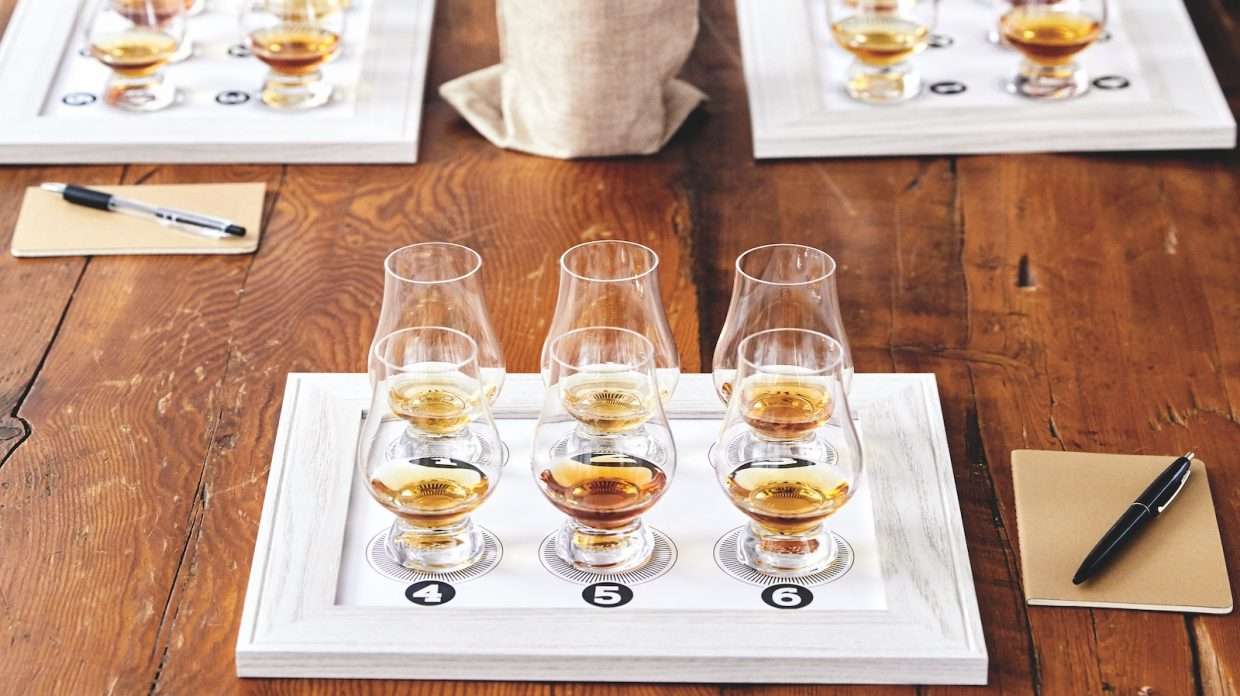 A flight of six whiskies in Glencairn glasses on a tasting mat with a pen and notebook