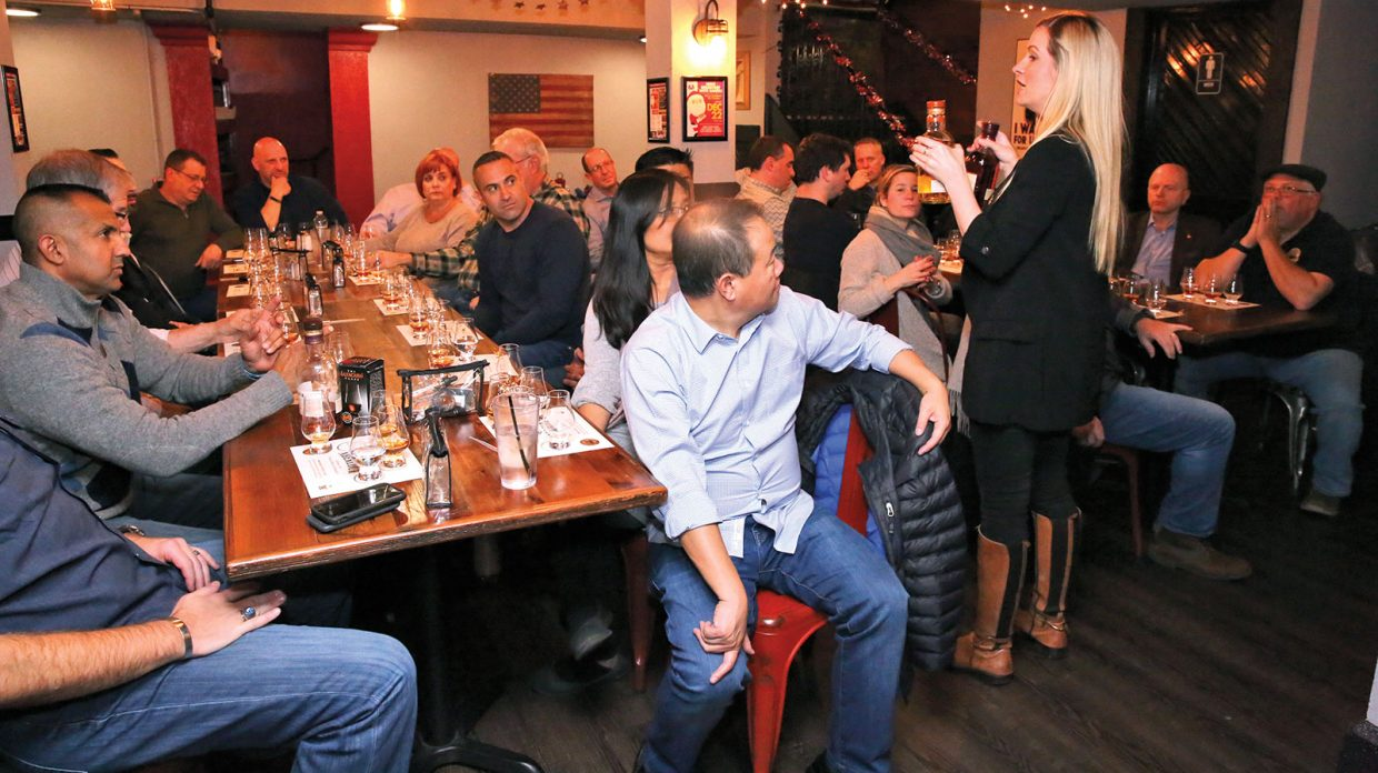 Monmouth Whisky Club members sit around two large rectangular wooden tables at Old Glory Kitchen + Spirits in Keyport, New Jersey, on an unspecified date, with Glencairn glasses containing what appears to be an assortment of whiskies in front of them during a single malt tasting led by Aberlour national brand ambassador Gemma Cole, who stands between the tables holding up two bottles and speaking to the group.