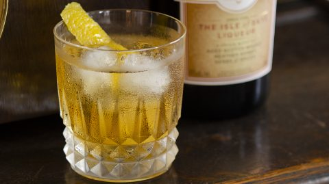 Rusty Nail cocktail with a lemon peel garnish and bottle of Drambuie