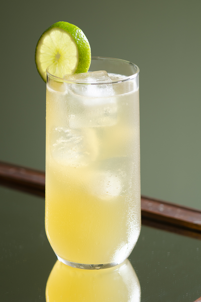 Collins glass filled with Whiskey Collins cocktail and garnished with a lime wheel