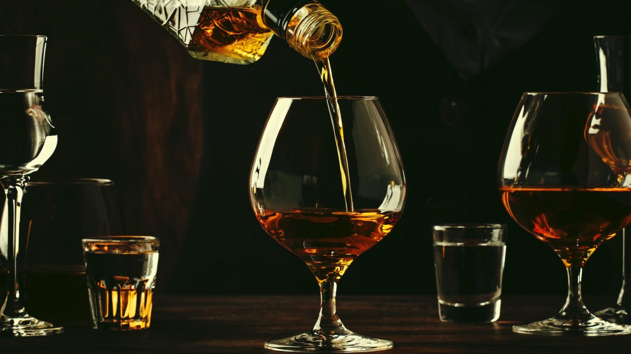 Cognac or brandy is poured into a glass sitting center on a bar, with small shot glasses and other glasses of brown liquid sitting on both sides of it.