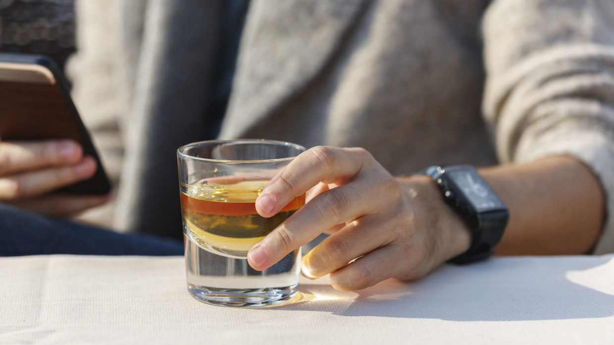 A man is holding his cell phone and reaching for a glass of whisky.