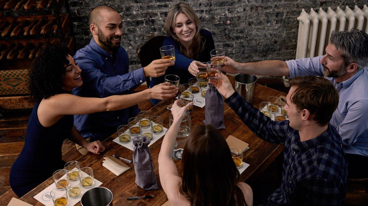 A group of people clink glasses at a table.