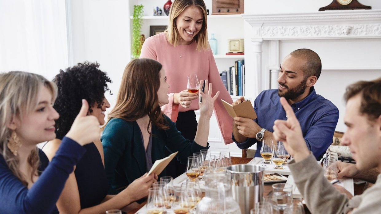 A group of six friends sits around a table to enjoy a whisky tasting.