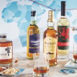 World whiskies from Japan, India, France and Wales alongside glasses of whisky, pairing snacks, and airline props.